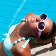 Beautiful young woman relaxing near the swimming pool — Stock Photo