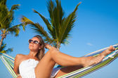 Woman lying in a hammock on a beach — Stock Photo