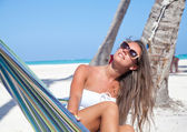 Young woman lying in a hammock on a beach — Stock Photo