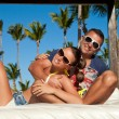 Sexy young couple relaxing near pool on a beach bed — Stock Photo