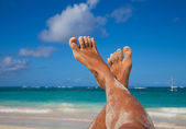 Young woman legs sunbathing on the beach — Stok fotoğraf