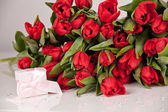 Picture of beautiful tulips with gift box, indoor decorations. — Stock Photo