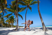 Man giving piggyback ride to girlfriend at the Caribbean beach — Stock Photo