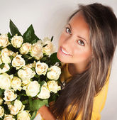 Pretty brunet woman holding bunch of roses — Stock fotografie