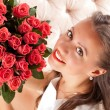 Beautiful woman with a bouquet of roses — Stock Photo #47319313
