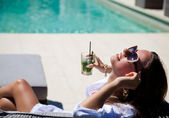 Sexy girl with a cocktail near the pool — Stock Photo