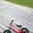 Red bike for kid on wooden floor — Stock Photo