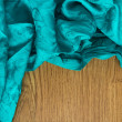 Colorful textile close up in bright green-blue on wood — Stock Photo