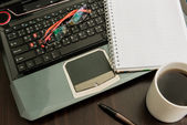 Coffee cup, laptop, pen , notepad and glasses on wooden table — Stock Photo