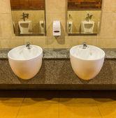 Lavandini bianchi e sapone liquido in bagno pubblico — Foto Stock