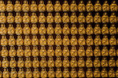 Golden buddhas lined up along the wall of chinese temple — Stock Photo