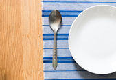 White plate and silver spoon — Stock Photo