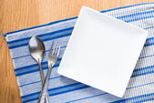 White plate and silver spoon and fork — Stock Photo