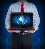 Businessman holding a laptop showing business graph — Stock Photo