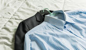 Men's classic shirts and suit on the bed — Stock fotografie