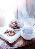 Chocolate chip cookies on napkin and hot tea on wooden table. — Stockfoto