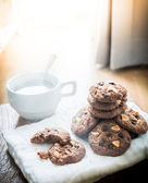 Chocolate chip cookies on napkin and hot tea on wooden table. — Stock Photo