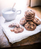 Chocolate chip cookies on napkin and hot tea on wooden table. — Zdjęcie stockowe