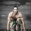 Постер, плакат: Muscle athlete with camouflage pants looking at camera and weigh tlifting