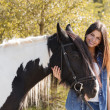 Portrait of beautiful young female rider embracing her horse and looking at camera — Stock Photo