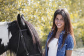Cropped portrait of beautiful brunette girl smiling and embracing her horse — Stock Photo