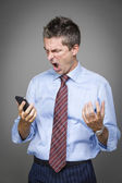 Very angry well-dressed businessman shouting on the phone — Stock Photo