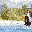 Beautiful Female horse rider crossing river in a mountainous lan — Stock Photo #32545263