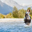Smiling Female horse rider crossing river in a mountainous lands — Stock Photo #32545415