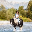 Beautiful Female sitting on horse while crossing river in a moun — Stock Photo