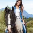 Young girl sitting on horse while crossing river in a mountainou — Stock Photo #32545645