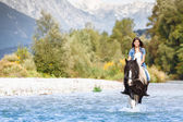 Beautiful Female horse rider crossing river in a mountainous lan — Stock Photo