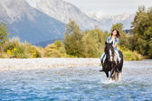 Smiling Female horse rider crossing river in a mountainous lands — Stock Photo