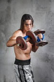 Muscular boxer working out with weights — Stock Photo