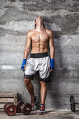 Muscular boxer man standing on the wall — Stock Photo