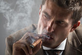 Hard gaze businessman while smoking a cuban cigar — Stock Photo