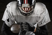 Portrait of american football player holding a ball and looking — Stock Photo