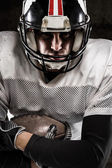 Portrait of american football player holding a ball — Stock Photo