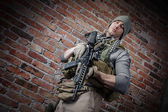 Portrait fo soldier with rifle looking at camera — Stock Photo