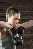 Young fit woman lifting kettle bell on brick background  — Stock Photo