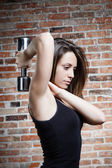 Young beautiful fit woman lifting dumbbells — Stock Photo