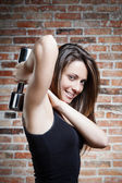 Young smiling fit woman lifting dumbbells — Stock Photo