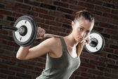 Sweat fit woman lifting dumbbells on brick background — Stok fotoğraf