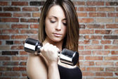 Young fit serious woman lifting dumbbells — Stockfoto