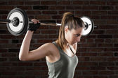 Attractive fit woman lifting dumbbells on brick background  — Stockfoto