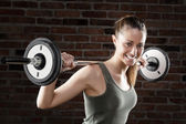 Smiling Sweat beautiful girl lifting dumbbells — Stockfoto