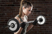 PSweat beautiful girl lifting dumbbells on dark background — Stockfoto