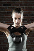 Young fit woman lifting kettle bell and looking at camera — Stockfoto