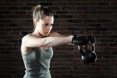 Young fit woman lifting kettle bell  — Stock Photo