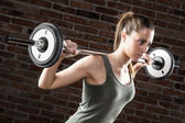 Sweat beautiful girl lifting dumbbells on brick background — Stockfoto
