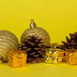 Small bright gift boxes, Christmas decorations and pine cones on a yellow background — Stock Photo
